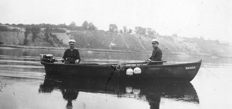 Dwóch przedwojennych policjantów płynie łodzią motorową