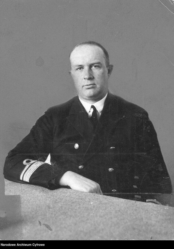 Mężczyżna w mundurze oficera marynarki siedi przy stole